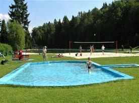 Nedaleké přírodní koupaliště s dětským bazénem a volejbalovým hřištěm