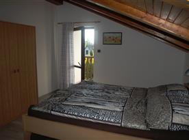 ložnice s manželskou postelí a balkonem