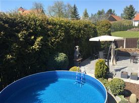 Pohled na bazén s posezením a zahradním grilem