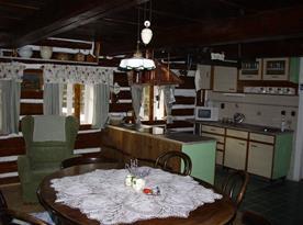 Pohled ze společenské místnosti na jídelní a kuchyňský kout