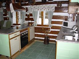 Pohled na kuchyňský kout s varným ostrůvkem a digestoří