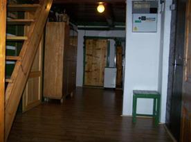 Vstupní chodba chalupy se skříní a vstupem do patra