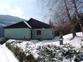 Zimní pohled na chatu, z které lze vidět lyžařské středisko Kouty