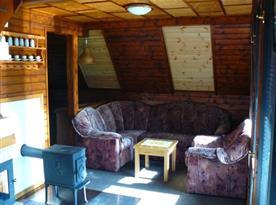 Obývací pokoj se sedací soupravou, stolkem a kamny