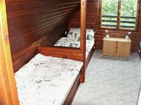 Podkrovní ložnice s lůžky, skříňkou a lampičkou