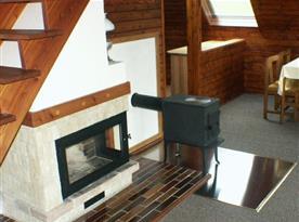 Obývací pokoj se stolem, židlemi, skříňkou, kamny a schody do podkroví