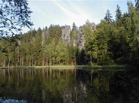 Jezírko za chalupou obklopené lesem a skalami