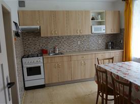 Kuchyně se sporákem, kamny, lednicí, varnou konvicí a jídelním koutem