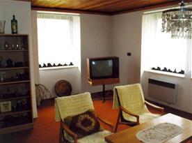 Obývací pokoj s pohovkou, stolkem, křesly a televizí