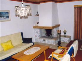 Obývací pokoj s pohovkou, stolkem, křesly a krbem