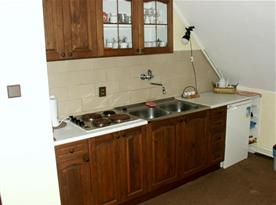 Kuchyňka s varnou deskou, ledničkou, varnou konvicí a remoskou