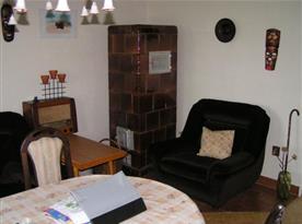 Obývací pokoj s gaučem, křeslem, stolem, židlem a kamny