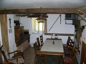 Společenská místnost má kachlová kamna, dva velké stoly, židle, křeslo a televizi