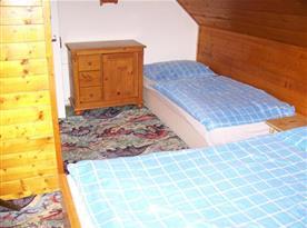 Podkrovní pokoj s lůžky, skříňkou a stoličkou