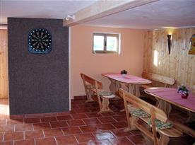 Společenská místnost s dřevěným posezením a šipkami v suterénu