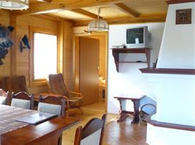 Osmilůžková chata - obytná místnost se stolem, židlemi, krbem a televizí