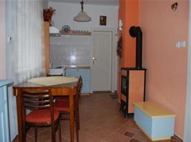 Kuchyně se sporákem, ledničkou, varnou konvicí, kamny, stolem a židlemi