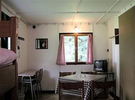 Chatka s patrovou postelí, stolem, židlemi, televizí a bez koupelny