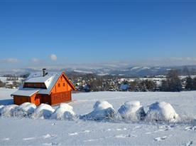 Pohled na roubenku a zimní okolí