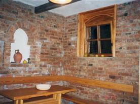 Vinný sklípek s dřevěnou lavicí a stoly