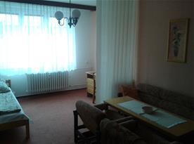 Obývací pokoj se sedací soupravou, skříňkou a televizí, psací stůl.