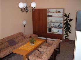 Obývací pokoj se sedací soupravou, stolkem, televizí a skříňkou