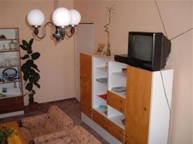 Obývací pokoj se sedací soupravou, skříňkou a televizí