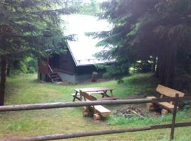 Pohled na chatu, posezení a ohniště z lesa