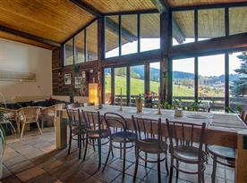 Velká obytná hala s prosklenou terasou, krbem, sedačkou a masivním stolem