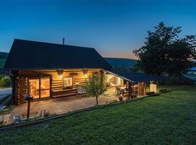 Večerní pohled na srub s rozsvícenou terasou