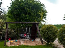 Dětské hřiště s trampolínou na zahradě před pensionem.