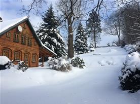Zasněžená zahrada s chalupou během zimy