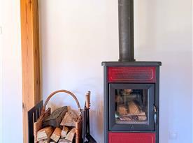 Kamna umístěna v obývacím pokoji s kuchyňským koutem