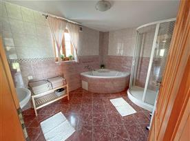 V koupelně se nachází rohová vana, sprchový kout, umyvadlo se zrcadlem a topení na ručníky s podlahovým vytápěním