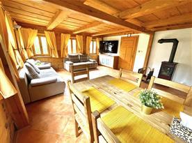 Obývací pokoj s kuchyňským koutem. Celá místnost je vytápěná kamny a podlahovým vytápěním.
