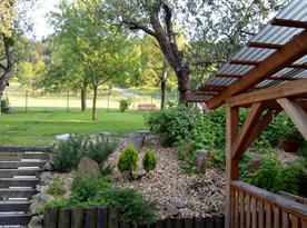 Pohled na oplocenou zahradu s bazénem, trampolínou a průlezkami