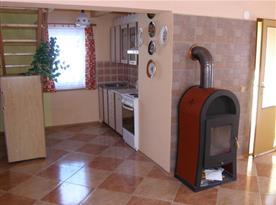 Kuchyňský kout a obytná místnost s krbem