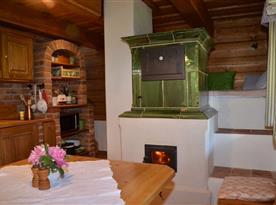 Sednice s jídelním koutem, kuchyňskou linkou a kachlovými kamny