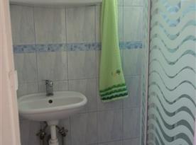 Koupelna se sprchovým koutem, teplá voda, umyvadlo, zrcadlo, dlažba. Moderní splachovací WC v oddělené místnosti.