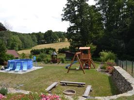 Zahrada s bazénem, ohništěm a skluzavkou s houpačkami