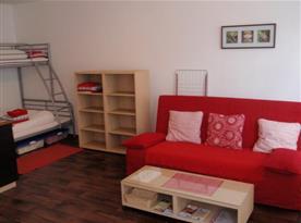 Obytná místnost s lůžky a sedací soupravou
