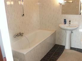 Koupelna pokoje B s vanou, umyvadlem a zrcadlem