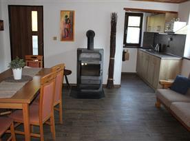 Společenská místnost s krbovými kamny a jídelní sestavou