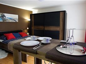 Barový stůl a manželská postel v pokoji