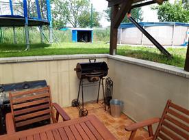 Zastřešené venkovní posezení s výhledem na bazén a trampolínu