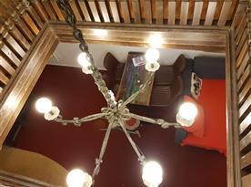 Pohled z patra do společenské místnosti s krbem