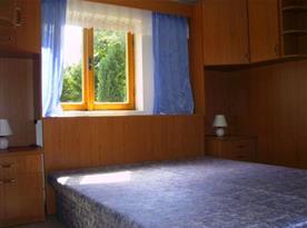 Ložnice s manželskou postelí a nočním stolkem