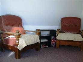 Menší společenská místnost s křesly a stolkem
