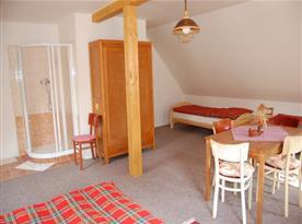 Ložnice s lůžky, stolem, židlemi, skříní a sprchovým koutem