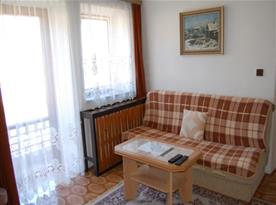 Apartmán v podkroví - pokoj B s sedačkou, stolkem, televizí a vstupem na balkón